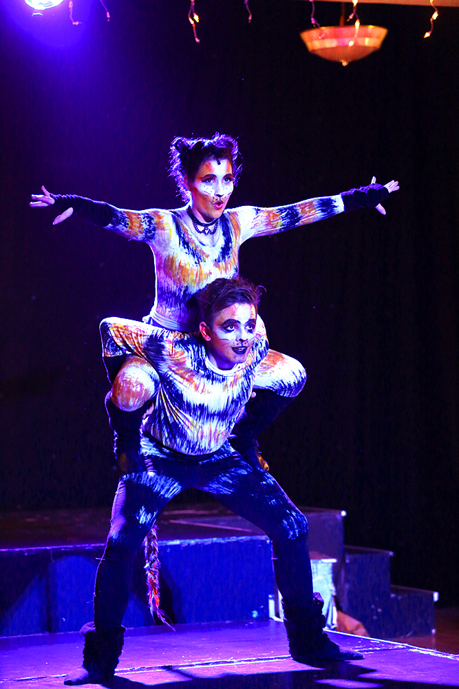 Nine Lives dancers in full costume, showing off a lift mid show.